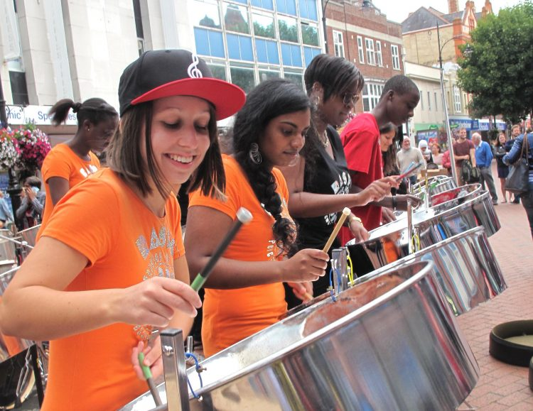 Young women play steel pan music in a shopping centre