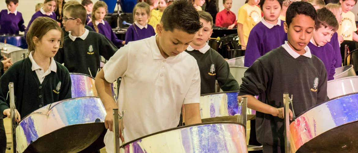 Children playing steel pan drums in an orchestra by CultureMix Arts Ltd