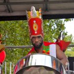 London Notting Hill Carnival 2018 RASPO Steel Band float with Daron wearing carnival head dress playing steel pan drum by CultureMixArts