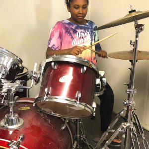Girl learning to play the drum kit at drum lessons with CultureMix