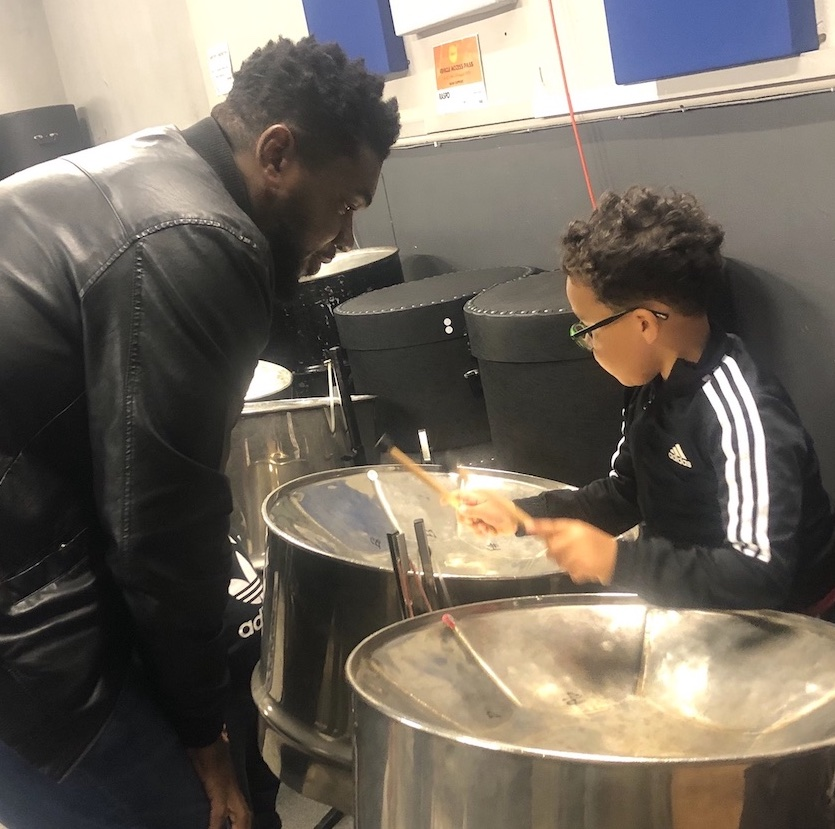 Image shows a father helping his five year old son to learn the steel pan at a RASPO Steel Band workshop in Reading UK