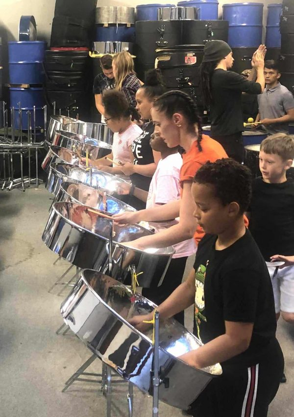 The image shows children, young people, adults and elders learning to play steel pan musical instrument at a RASPO Steel Band workshop in Reading UK