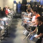 Group of children, young people, adults and elders playing steel pan music at a workshop