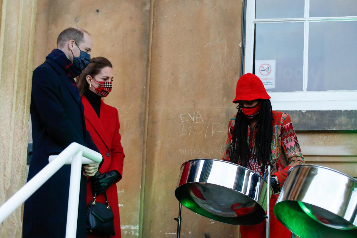 A royal couple watch a steel pan player